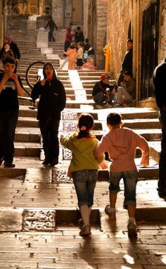 Arab girls running arm in arm through the Old City