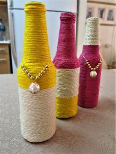 Trio de garrafas decoradas com linhas amarela,branca e rosa