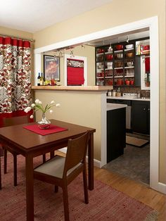 I think the pops of red are flatteringly eye catching and transform the neutral paint colors into a snazzy space. I particularly love the mosaic back splash. I like that the red becomes the accent as you transition into the kitchen allowing black to become the new focal color.I would be sure to include some tan accents to keep the kitchen tied into the overall public area color scheme.