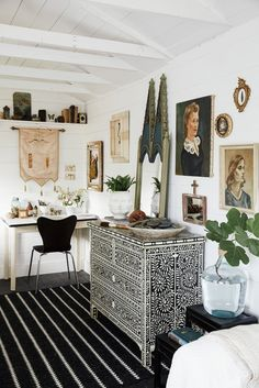 A pearl-inlay dresser, vintage paintings, and plants make the room feel rich and full of character. Source:...