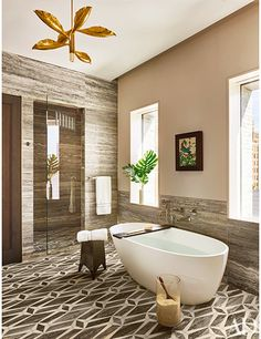 Travertine wall panels and a geometric stone-tile floor lend warm tones to the master bath; the vintage light fixture is by Angelo Lelli, the framed collage is by Mark Welsh, the tub is by Wetstyle, and the tub fittings are by Kallista.
