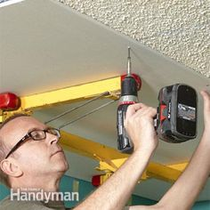 Driving drywall screws when covering a popcorn ceiling with drywall.