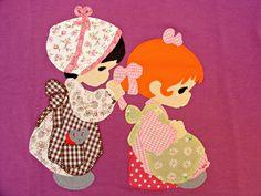 Detalle de camiseta morada con dibujo de aplicaciones patchwork de una niña peinando a otra.