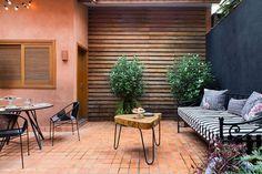 Área externa de casinha de vila tem banco de ferro e mesa de madeira para café da manhã.