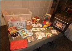 Food/Cooking Bin picture 1-Food games, crafts, puzzles, food related play dough materials, cash register, cardboard box, stove, play food. (store, table chairs, dishes, chef hat, apron, big box pizza hut in other pictures).