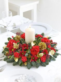 This sumptuous arrangement of flowers and foliage is a fitting decoration for the Christmas dinner table and is sure to be admired by all. We've chosen festive red flowers and a selection of seasonal foliage and added a chunky cream candle as the centre piece.<br /><br />Featuring 4 red carnations, 1 red spray chrysanthemum, 1 burgundy skimmia spray, 2 red spray carnations with spruce, holly and gold eucalyptus. The design is finished with a chunky cream 100% wax candle and gold glittered…