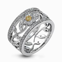 This charming white gold vintage style ring features a lovely floral design accented by .77 ctw of round cut white diamonds and .02 ctw round cut yellow diamonds.