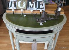 We think the Grand Illusions Vintage Paint in 'Chapel' goes really well with the original green top on this demi lune table.