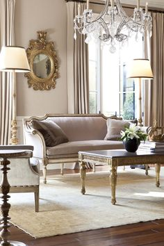 Bergamo settee, gilded Sorriso mirror, Bardot rock crystal chandelier, Montaigne cocktail table, Naples floor lamp, Viceroy chair and Tuilleries side table.