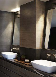 Deux vasques blanches et décoration sombre de cette salle de bains