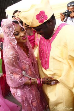 Pink Nigerian bride with hijab head cover. Muslim wedding. Hand henna. Nigerian groom in light yellow traditional wear.