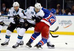 San Jose Sharks forward Eriah Hayes puts a body check on New York Rangers forward Chris Mueller (Oct. 19, 2014).