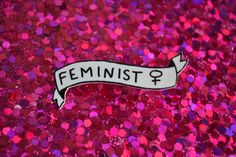 Proud Feminists everywhere! Tell the world whats up. The Feminist banner pin is hand-illustrated on shrink plastic by me, and includes a
