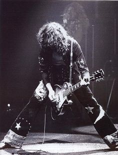 Date: Circa 1972 | Jimmy Page performing of Led Zeppelin | Robert Plant is also seen in the background.