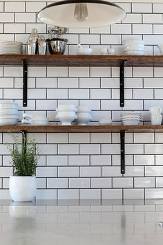 Kitchen design ideas including subway tile with black grout and rustic industrial wood shelves
