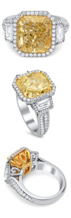 This platinum and 18K gold ring boasts a 7.01 carat radiant cut Fancy Light Yellow diamond framed by a delicate halo of round white diamonds. The extremely rare knockout diamond is flanked by a pair of tapered baguettes that are also framed by individual halos of white diamonds. The fancifully designed shank is graced with additional white diamonds while the ring's gallery showcases an aesthetic of curlicues and eyelets adorned with Fancy Intense Yellow diamonds and round white diamonds.