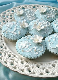 blue embossed fondant beauties with white brushed lace flowers, scrollwork and fondant blossom and pearls.  SO pretty.  Looks like thy were sprayed with lustre before white work was done.