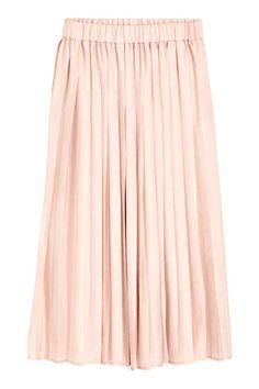 Falda plisada: Falda plisada en tejido vaporoso con cintura elástica. Largo hasta la pantorrilla.