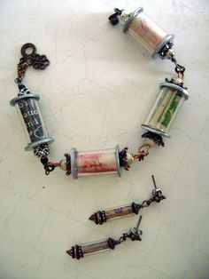 Paper beads inside plastic tubing (Michaels sells cylinders like these - Bead Landing™ Found Objects™ Glass Capsule Charms)