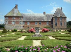 Château de Carrouges: Flowerbed in the garden and facade of the château; in the Normandie-Maine Regional Nature Park - France-Voyage.com