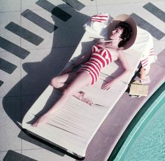 Austrian actress Mara Lane lounging by the pool in a red and white striped bathing costume at the Sands Hotel, Las Vegas, 1954.