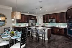 Love the Dark Cabinets with the Aqua Colored Backsplash ~ Cool Gold Light Fixture Over the Table!