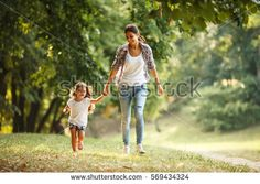 Mother and daughter playing and running around the park on beautiful morning.