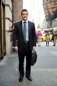 Fund manager, Claus Heimann, likes to wear Ralph Lauren. Here he is seen wearing a navy blue suit, black shoes and a black leather briefcase. His shirt is striped blue with a formal white collar, his tie is green, and to cap it all off he's sporting a fetching cropped haircut.