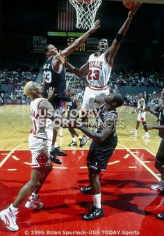 Dennis Rodman positions himself for a possible rebound while Michael Jordan delivers a lefty layup against the Kings in Chicago.