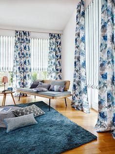 Estores de rayas y dobles cortinas de flores azul en el salón - Villalba Interiorismo