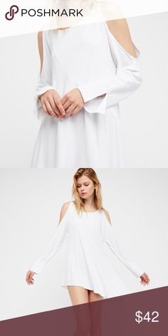 white tunic • free people Cold shoulder solid tunic featuring adjustable ties at the shoulders.  Long sleeves with a ruffle cuff Slightly stretchy fabric Asymmetrical hem Styling Tip: This versatile top can also be worn as a super mini dress. For a no-show look layer with one of our seamless shorts for an effortless look. Free People Tops Tunics