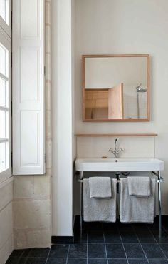 i like the wood mirror, grey towels, and blue tiles