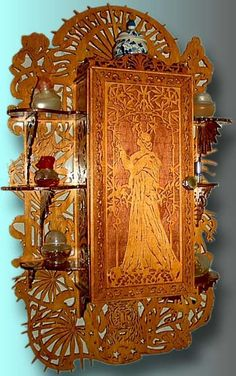 This is an alluring art nouveau wall cabinet. The cabinet is in the center and three shelves on each side complete the design. Its ornamentation is fully in art nouveau style. It contains a large number of different leaves and flowers, and a curious tiger in the lower part. The door of the cabinet contains a beautiful fretworked panel showing a lady in a garden.