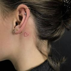 Red ink heart outline tattoo behind the left ear.