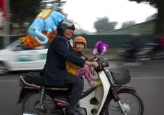 Father and child on a moped in Hanoi, Vietnam - Vater und Kind fahren mit dem Moped in Hanoi, Vietnam