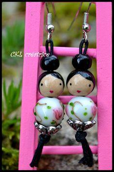 Boucles d'oreilles poupée perles bois et verre. Les perles en bois sont peintes et vernies à la main. Les boucles d'oreilles mesurent 6 cm au total. Perles visage (10mm), perles corps verre (12mm), coupelles métal argenté. Elles sont livrées dans une jolie petite boîte. Fait main.