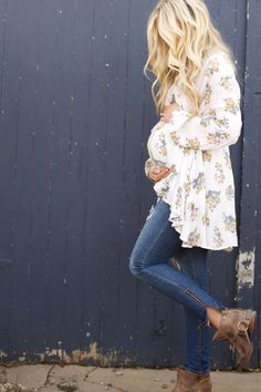 A floral tunic paired with jeans and pixie boots makes a trend worthy pregnancy outfit.