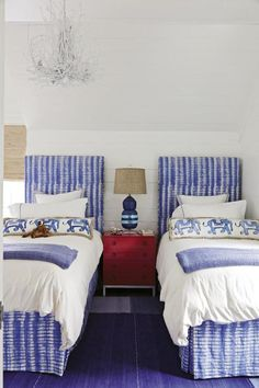 Cottage home with blue and red kids' room features white paneled ceiling and walls lined with a pair of matching white and blue headboards on twin beds…