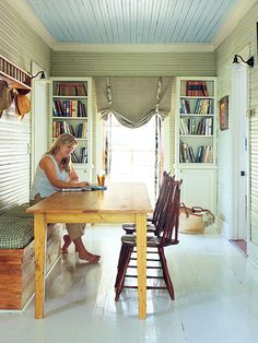 The center entry hall of this Magnolia Springs, Alabama, home serves double duty as the dining room. A fresh coat of green paint gives the original beaded board of this 1903 cottage new life, as does a coat of white on the floors. (Photo: Roger Davies)