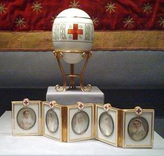 The Red Cross with Imperial Portraits Egg is a jeweled & enamel egg made in 1915.  Made for the Dowager Empress Marie. The surprise inside was a hinged, folding screen of five oval miniatures of women from the Russian Imperial family, each wearing the uniform of the Red Cross. The portraits depict Olga Alexandrovna (Nicholas II's sister),  Olga & Tatiana (Nicholas II's eldest daughters), Empress Alexandra Feodorovna, and Grand Duchess Maria Pavlovna (Nicholas II's first cousin).