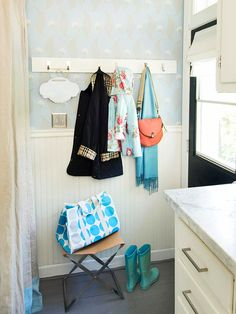 This small entry makes the most of limited space with a few smart solutions. Using wall pegs is a way to organize outerwear, and a folding stool adds the functionality of a bench but can be tucked away when not in use.