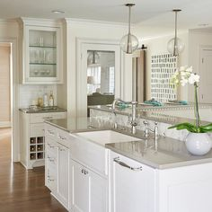 Beautiful kitchen features a white kitchen island topped with gray quartz fitted with a farmhouse sink and a vintage style faucet illuminated by Arteriors Caviar Pendants.