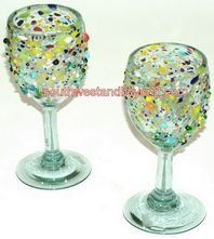 """Mexican Bubble Glass - Mexican Glassware Pitcher Sets and Glasses . $20.00. Add life and flavor to your home, special occasion or party with these beautiful hand blown wine goblet glasses. It has an amazing and original pebbled paint spots finish at the top. These glasses are sold in sets of two, so the price shown is for two glasses. Due to the hand blown nature of our glassware please expect slight variations in size and shape.Height 7"""" Width 3"""" Model: 050-A Confett..."""