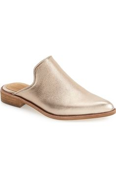 A sinuous topline and a dramatic pointy toe define this day-to-night mule in metallic gold crafted with a generously padded footbed and a low stacked heel.
