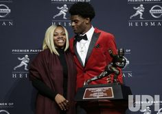 Louisville Cardinals quarterback Lamar Jackson stands with mom Felicia James as he holds the Heisman trophy at a press conference at the…
