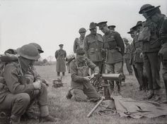 King George VI inspects Australian soldier assembling Vickers machine gun whilst blindfolded