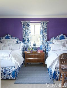 Blue and white floral against purple walls energizes a bedroom by designers Kirsten Fitzgibbons and Kelli Ford.