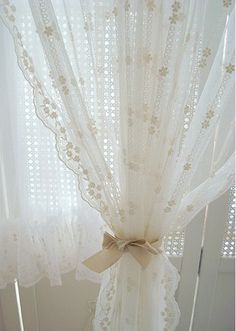 I have a vintage-looking white curtain styled like this over my master bathtub--love the romance of it
