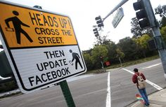 """In order to fight the phenomenon of """"deadwalkers"""" – walking by being distracted by one's phone – as it is the new hip reason for an ER trip, various slogan have been invented, like """"don't drive intexticated"""". Additionally, signs have been put up with messages similar to the one in this photo."""