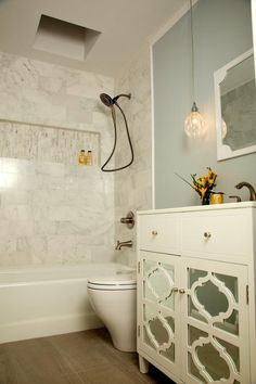 HGTV features a transitional blue bathroom with a gorgeous marble shower and charming furniture-style vanity.